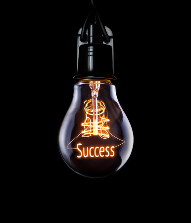 favourable: Hanging lightbulb with glowing Success concept. Stock Photo