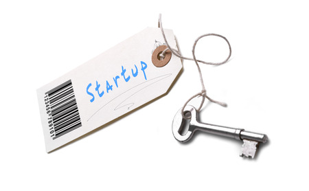 A silver key with a tag attached with a Startup concept written on it.