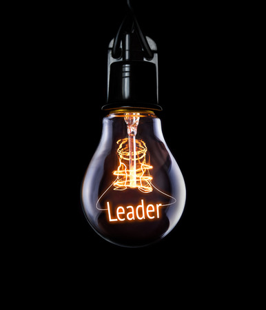 Hanging lightbulb with glowing Leader concept.