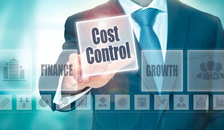 A businessman selecting a Cost Control Concept button on a clear screen. Foto de archivo