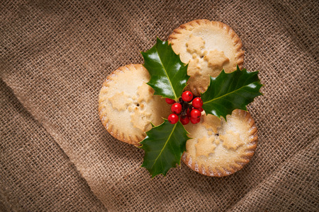 Close up of Christmas Mince Pies and holly sprig on a natural hessian background