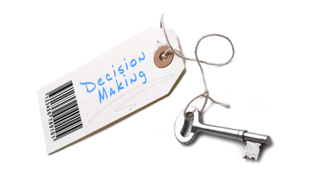 A silver key with a tag attached with a Decision Making concept written on it.
