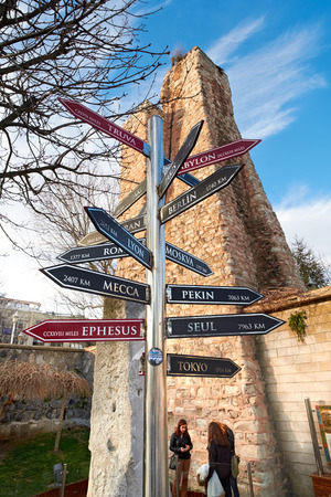 ISTANBUL, TURKEY - FEBRUARY 12, 2014: Tourists behind a signpost to world cities in Istanbul,Turkey. Editorial