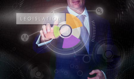 A businessman selecting a Legislation button on a computerised display screen. Stock Photo