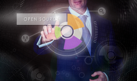 software portability: A businessman selecting a Open Source button on a computerised display screen. Stock Photo