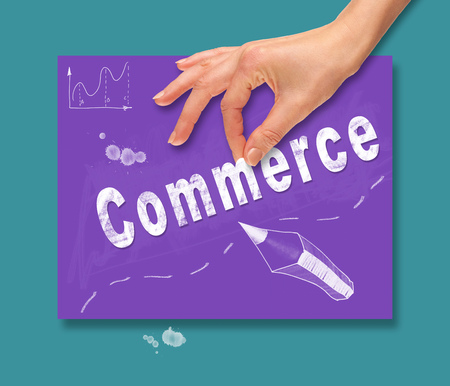 electronic commerce: A hand picking up a Commerce concept on a colorful drawing board.