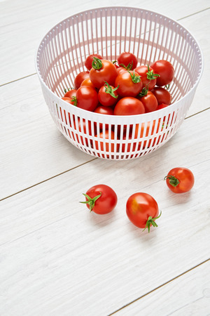 Fresh ripe red tomatoes in a colander on a pale wood work surface, worktop background Stock Photo