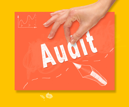 A hand picking up a Audit concept on a colorful drawing board.