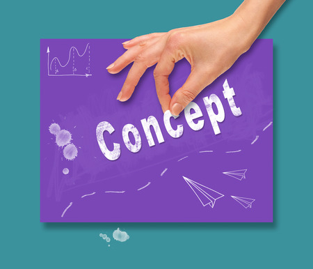 A hand picking up a concept on a colorful drawing board. Stock Photo
