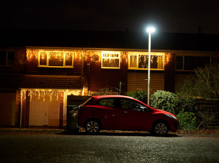 A car sat under the security of a street lamp with Christmas lights on the house behind it. Standard-Bild