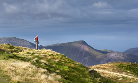 LAKE DISTRICT, CUMBRIA, ENGLAND, UK - OCTOBER 08, 2016: An elderly hiker taking in the views from the summit of Dale Head in the Lake District, England, UK.