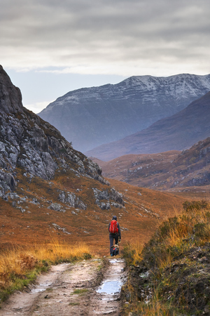 A hiker walking towards the summits of Beinn Dearg Mor and Beinn Dearg Bheag with the river Gruinard just out of sight. Scottish Highlands, Scotland, UK. Stock Photo