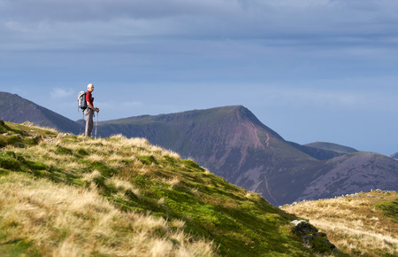 cumbria: LAKE DISTRICT, CUMBRIA, ENGLAND, UK - OCTOBER 08, 2016: An elderly hiker taking in the views from the summit of Dale Head in the Lake District, England, UK.