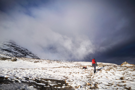 A hiker walking along the mountain path  route on Beinn Eighe, Scottish Highlands, Scotland, UK. Stock Photo