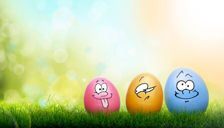 Colourful painted Easter Eggs with a family of cartoon funny faces on green grass and blurred garden and sky background.