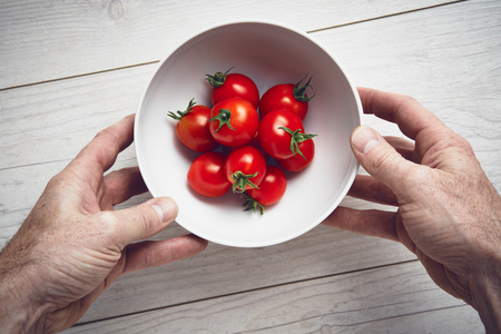 table top: A mans hands picking up a white bowl of bright red ripe tomatoes on a pale wood work surface, worktop in a kitchen.