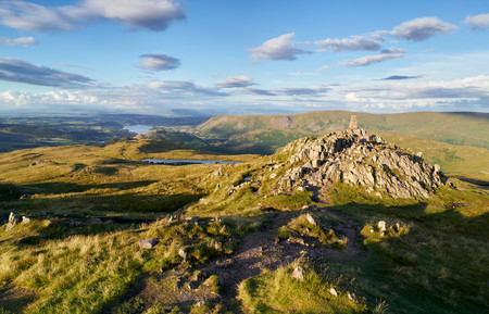 cumbria: The mountain summit of Place Fell in the Lake District at sunset.