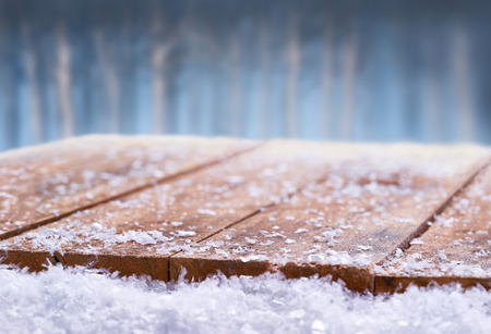 Wooden table top covered in snow with a Christmass, winter and snowy background with space to add products and text.