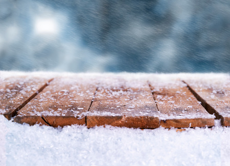 Wooden table, bench covered in snow with a Christmass, wintery and snowy background with space to add products and text.                           Stock Photo