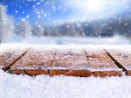 Wooden table, bench covered in snow with a Christmass, wintery and snowy background with space to add products and text.                           Stockfoto