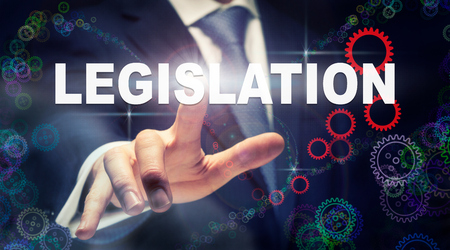 A hand selecting a Legislation business concept on a clear screen with a colorful blurred background. Imagens