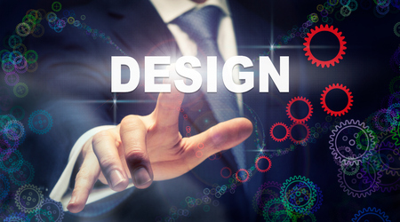 A businessman pressing a Design business concept on a graphical display of cogs Stockfoto