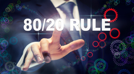 A businessman pressing a 8020 Rule business concept on a graphical display of cogs