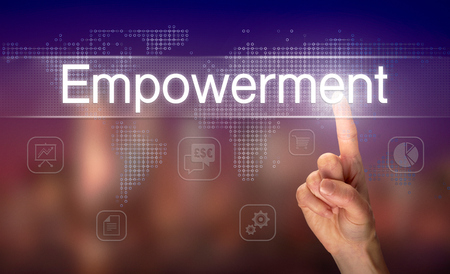 A hand selecting a Empowerment business concept on a clear screen with a colorful blurred background. Stok Fotoğraf