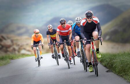 Cyclists out racing along country lanes in the mountains in the United Kingdom. 免版税图像