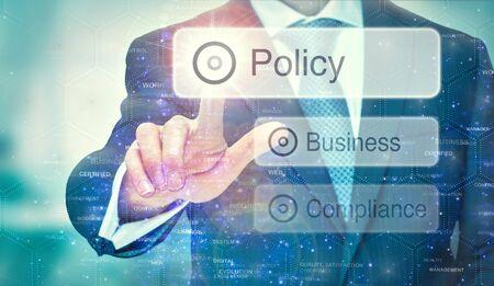 Un homme d'affaires sélectionne un bouton Politique sur un écran futuriste avec un concept écrit dessus.