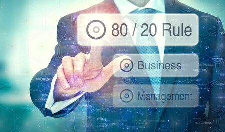 A businessman selecting a button on a futuristic display with a 80 / 20 Rule concept written on it.