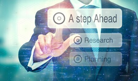 A businessman selecting a button on a futuristic display with a A Step Ahead concept written on it. Stock fotó