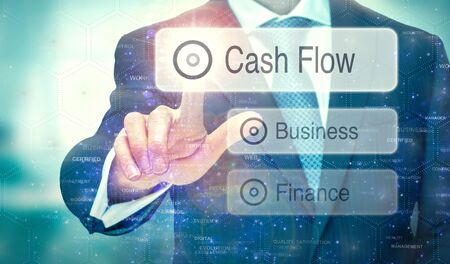 A businessman selecting a button on a futuristic display with a Cash Flow concept written on it.