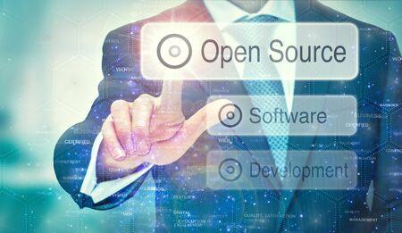 Ein Geschäftsmann wählt eine Open-Source-Schaltfläche auf einem futuristischen Display mit einem darauf geschriebenen Konzept aus. Standard-Bild
