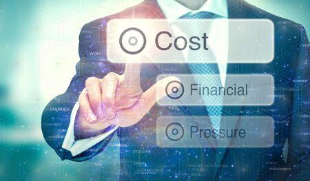 Ein Geschäftsmann, der eine Schaltfläche auf einem futuristischen Display mit einem darauf geschriebenen Kostenkonzept auswählt. Standard-Bild