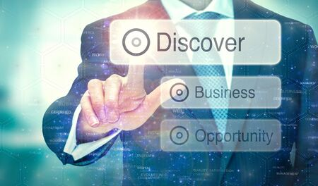 A businessman selecting a button on a futuristic display with a Discover concept written on it.