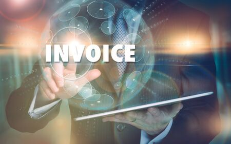 A hand selecting a Invoice business concept on a futuristic computer display. Stock Photo
