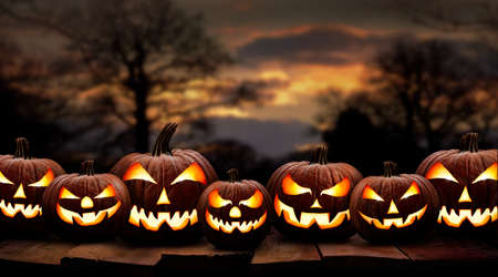 Seven spooky halloween pumpkin, Jack O Lantern, with an evil face and eyes on a wooden bench, table with a sunset, night background.