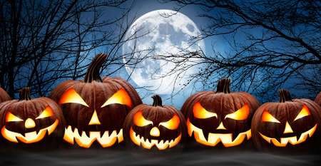 Five spooky halloween pumpkins in a row, Jack O Lantern, with evil face and eyes on a wooden bench, table with a misty night forest and full moon background