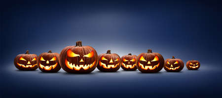 Eight halloween, Jack O Lanterns, with evil spooky eyes and faces isolated against a blue lit background.