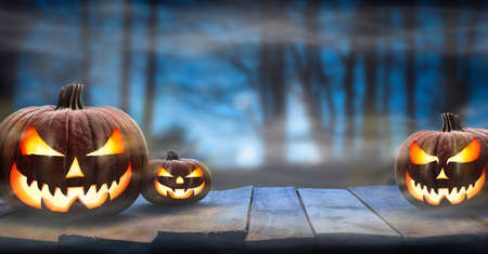 Three spooky halloween pumpkins, Jack O Lantern, with evil face and eyes on a wooden bench, table with a misty night forest background with space for product placement.