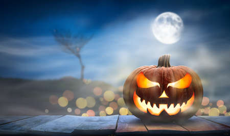 One spooky halloween pumpkin, Jack O Lantern, with an evil face and eyes on a wooden bench, table with a misty night background with space for product placement. Stockfoto