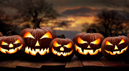 Five spooky halloween pumpkin, Jack O Lantern, with an evil face and eyes on a wooden bench, table with a sunset, night background. Stockfoto