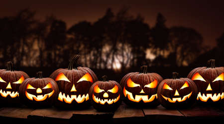 Seven spooky halloween pumpkin, Jack O Lantern, with an evil face and eyes on a wooden bench, table with a sunset forest night background. Stockfoto