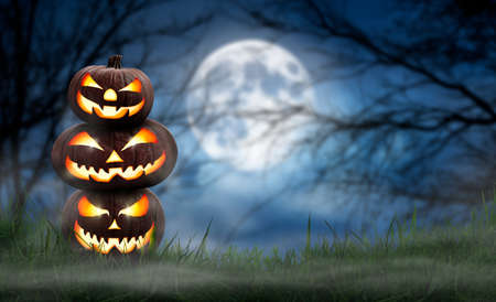 A pile of three spooky halloween pumpkin, Jack O Lantern, with an evil face and eyes on the grass with a misty night sky background with a full moon.