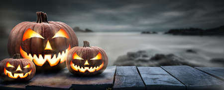 Three spooky halloween pumpkins, Jack O Lantern, with an evil face and eyes on a wooden bench, table with a misty gray coastal night background with space for product placement.