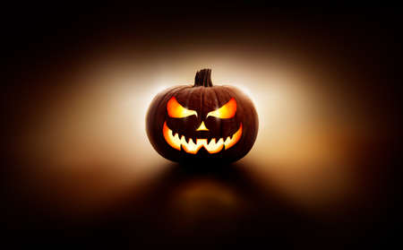 A back lit halloween lantern, Jack o Lantern, with a spooky evil face with glowing eyes against a dark background.
