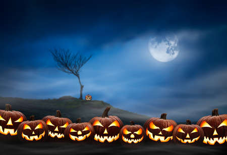 Lots of halloween lanterns with evil face and eyes, Jack O Lantern, against a spooky looking landscape background at night with a glowing full moon, lone tree and cloudy sky. Stockfoto