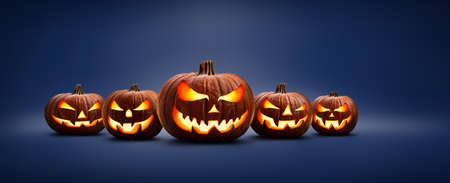 Five halloween, Jack O Lanterns, with evil spooky eyes and faces isolated against a blue lit background.