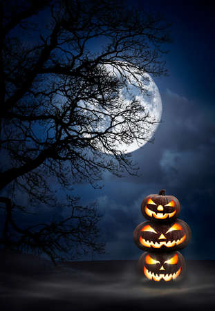 A pile of three spooky halloween pumpkins, Jack O Lantern, with evil face and eyes under the silhouette of a tree at night with a full moon and misty sky.